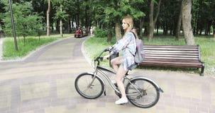 Glückliches Mädchen mit einem Rucksack fährt Fahrrad im Park stock footage
