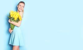 Glückliches Mädchen mit gelben Tulpen Hintergrund für eine Einladungskarte oder einen Glückwunsch Lizenzfreies Stockfoto