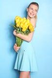 Glückliches Mädchen mit gelben Tulpen Hintergrund für eine Einladungskarte oder einen Glückwunsch Lizenzfreie Stockfotos