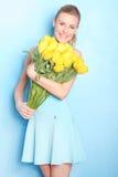 Glückliches Mädchen mit gelben Tulpen Hintergrund für eine Einladungskarte oder einen Glückwunsch Stockfotografie