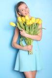 Glückliches Mädchen mit gelben Tulpen Hintergrund für eine Einladungskarte oder einen Glückwunsch Stockfotos