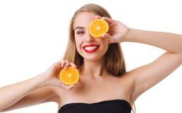 Glückliches Mädchen mit halber Orange zwei auf Weiß lokalisierte Hintergrund Lizenzfreies Stockfoto
