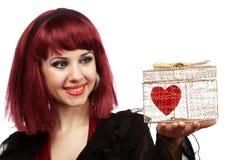 Glückliches Mädchen mit Innerem in einem goldenen Geschenkkasten Stockfotografie
