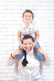 Mädchen, das auf dem Hals seiner Mutter sitzt Lizenzfreie Stockfotos