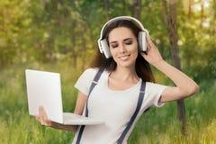 Glückliches Mädchen mit Kopfhörern und Laptop hörend Musik Lizenzfreies Stockfoto
