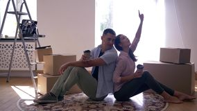 Glückliches Mädchen mit neuem Haus des Freundgeschmacks und trinkenden dem Kaffee, die auf Boden unter Kästen nach Verlegung sitz stock footage