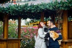 glückliches Mädchen mit Reisenfall Junge Paare auf dem Weihnachtsbasar mit Haustieren Lizenzfreies Stockbild
