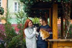 glückliches Mädchen mit Reisenfall Junge Paare auf dem Weihnachtsbasar mit Haustieren Stockbilder