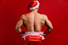 glückliches Mädchen mit Reisenfall sexy starker tragender Hut Weihnachtsmanns Junger muskulöser Mann Roter Hintergrund stockfotos