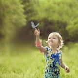 Glückliches Mädchen saß auf dem Arm eines schönen Schmetterlinges Stockfotos