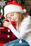 Glückliches Mädchen in Sankt-Hut mit Geschenken schlafend nahe Weihnachtsbaum Stockfoto