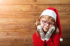 Glückliches Mädchen in Sankt-Hut und -handschuhen auf einem hölzernen Hintergrund, Kopie Stockfotografie