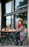 Glückliches Mädchen sitzt im Café auf der Straße von Budapest Lizenzfreie Stockbilder