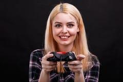 Glückliches Mädchen, Spiele mit einem Spielsteuerknüppel mit einem sehr emotionalen Ausdruck Schwarzer Hintergrund Lizenzfreie Stockfotos