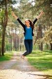 Glückliches Mädchen springt draußen in ein park_vertical Lizenzfreie Stockbilder