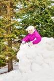 Glückliches Mädchen steht hinter dem Schneewandlächeln stockbilder