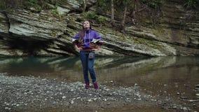 Glückliches Mädchen steht, setzend ihre Hände auf die Hüften durch den Gebirgssee und sie schaut oben stock footage