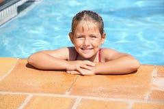 Glückliches Mädchen am Swimmingpool Stockbilder