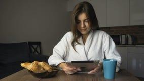Glückliches Mädchen trinkt Kaffee und benutzt Tablet stock footage
