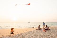 Glückliches Mädchen und Familie auf Sonnenuntergangstrand Stockbild