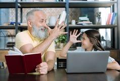 Glückliches Mädchen und ihr Großvater, die zusammen lustige Gesichter macht Stockbilder