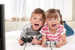 Glückliches Mädchen und Junge, die ein Videospiel spielt Stockfotografie