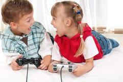 Glückliches Mädchen und Junge, die ein Videospiel spielt Lizenzfreie Stockfotografie