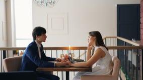 Glückliches Mädchen und Kerl der jungen Leute sprechen das Händchenhalten, das bei Tisch mit Blumen, Kerzen und Champagner in net stock video footage