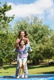 Glückliches Mädchen und Mutter, die hoch auf Trampoline im Park springt Lizenzfreie Stockbilder