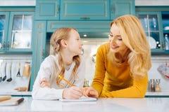 Glückliches Mädchen und Mutter, die zusammen Hausarbeit tut Lizenzfreies Stockbild