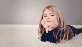 Glückliches Mädchen zu Hause, das auf Teppich legt Stockbilder