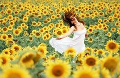 Glückliches Mädchen zwischen Sonnenblume Lizenzfreie Stockbilder