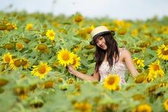Glückliches Mädchen zwischen Sonnenblume Lizenzfreie Stockfotografie