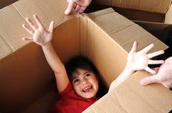Glückliches Mädchenfell innerhalb einer großen Pappschachtel, die in ein neues hou sich bewegt lizenzfreies stockbild