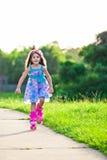 Glückliches Mädchenreiten auf Rollenblättern im Park stockbilder