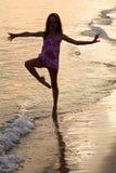 Glückliches Mädchentanzen auf dem Strand zur Sonnenuntergangzeit stockbild
