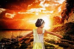 Glückliches Mädchentanzen, das bei magischem Sonnenaufgangsonnenuntergang genießt Stockfotos