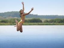 Glückliches Mädchenwasserspringen stockbild