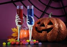Glückliches makabres Parteicocktail Halloweens trinkt mit skeleton Gläsern und Kürbis Stockfotografie