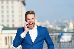 Glückliches Managergespräch auf Smartphone Mann mit Handy auf sonniger Terrasse Geschäftsmann in der blauen Klage im Freien Getre Stockfotos