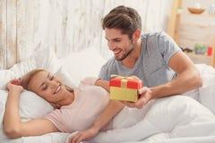 Glückliches Manngeben seiner Frau vorhanden lizenzfreie stockfotografie