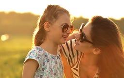 Glückliches Modekindermädchen, das ihre Mutter in der modischen Sonnenbrille umfasst Stockfotos