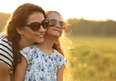 Glückliches Modekindermädchen, das ihre Mutter in der modischen Sonnenbrille umfasst Lizenzfreie Stockfotos