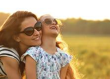 Glückliches Modekindermädchen, das ihre Mutter in der modischen Sonnenbrille umfasst Stockbild