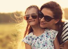 Glückliches Modekindermädchen, das ihre Mutter in der modischen Sonnenbrille umfasst Lizenzfreie Stockfotografie