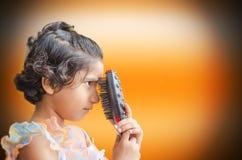 Glückliches Modemädchen, das mit Haarbürste spielt Stockbild