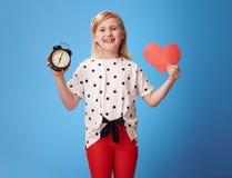 Glückliches modernes Kind, das Wecker- und Papierherz auf Blau zeigt Lizenzfreie Stockfotografie