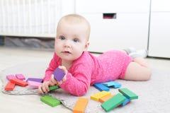 Glückliches 6-monatiges Baby spielt hölzernes mehrfarbiges meccano Stockfotos