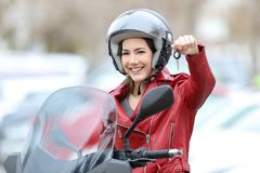 Glückliches motorbiker, das Schlüssel auf ihrem neuen Motorrad zeigt lizenzfreie stockfotos