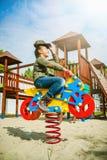 Glückliches Motorrad des kleinen Mädchens Reitauf Spielplatz allein im sonnigen Wetter Stockbild